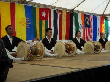 Student playing drums on a stage surrounded by flags