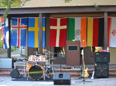 Image of several different flags hanging over a stage with musical instruments on it