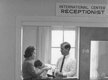 "A black and white photograph of a man and woman talking at a desk with a sign above that reads ""International Center Receptionist"""