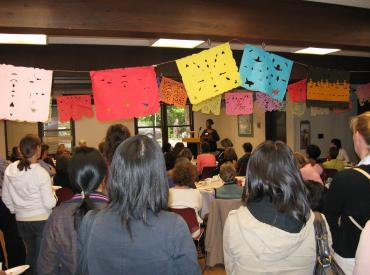 Audience members watching a speaker at an International Women's Day celebration