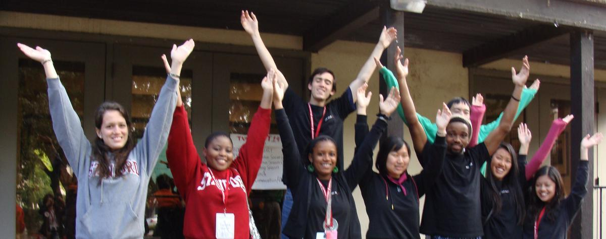 Students welcoming someone by excitedly raising their arms