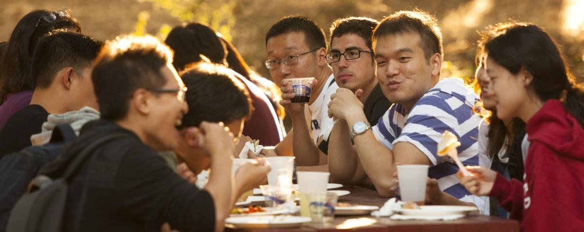 Students eating and talking at an outdoor table